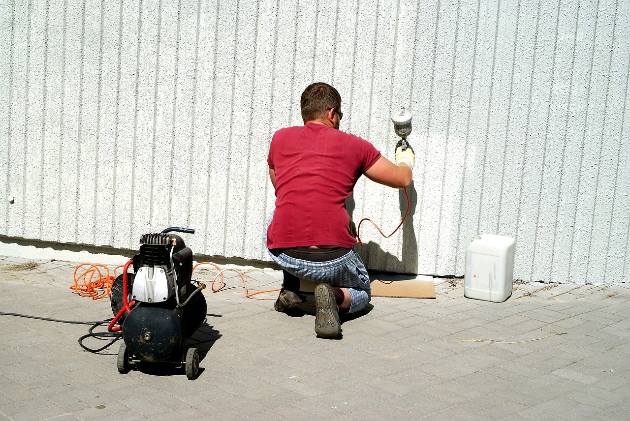 Man Spraypainting a House